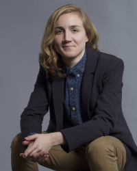 Recent Ph.D. in Feminist Studies | Long-haired person wearing blue blazer looks into camera while smiling