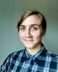white genderqueer person wearing white and blue plaid shirt looks into camera